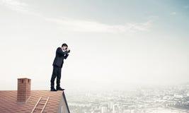 Ο κύριος προϊστάμενος στη στέγη τούβλου σε αναζήτηση κάτι νέου Μικτό medi Στοκ Εικόνες