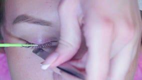 Ο κύριος σε ένα σαλόνι ομορφιάς αφαιρεί τα παλαιά eyelashes απόθεμα βίντεο
