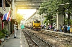 Ο κύριος σταθμός κυματίζει την πράσινη σημαία για να κάνει τη σηματοδότηση για να κάνει το τραίνο να αναχωρήσει άδεια στοκ εικόνα