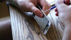 Ο κύριος, στερεώνει τα μικρά μέρη του σπασμένου τηλεφώνου, η οθόνη στην επιτροπή με ένα μικρό κατσαβίδι 4K 30fps απόθεμα βίντεο