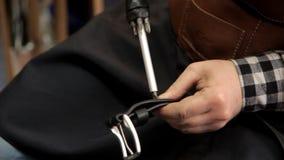 Ο κύριος στερεώνει την πόρπη στη ζώνη δέρματος Διαδικασία για τις ζώνες δέρματος απόθεμα βίντεο