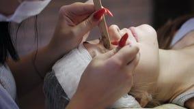 Ο κύριος στο σαλόνι ομορφιάς αφαιρεί τα παλαιά eyelashes, προετοιμάζοντας τον ασθενή για τη διαδικασία της επέκτασης eyelash απόθεμα βίντεο
