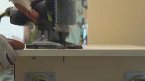 Ο κύριος της παραγωγής επίπλων πριονίζει την επιφάνεια του πίνακα με ένα ηλεκτρικό τορνευτικό πριόνι E o απόθεμα βίντεο