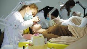 Ο κύριος των επεκτάσεων eyelash προετοιμάζεται για τη διαδικασία για την επέκταση eyelash φιλμ μικρού μήκους