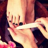 Ο κύριος Pedicurist κάνει το pedicure στα πόδια της γυναίκας Στοκ Φωτογραφία