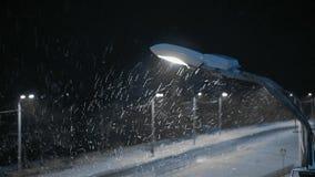 Ο λαμπτήρας οδών κινηματογραφήσεων σε πρώτο πλάνο φωτίζει το δρόμο στη χιονοθύελλα απόθεμα βίντεο