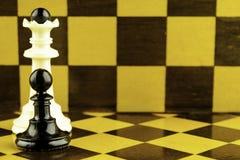 Ο λευκός βασιλιάς σκακιού και το μαύρο ενέχυρο στέκονται δίπλα σε ένα διάστημα αντιγράφων σκακιερών στοκ εικόνα με δικαίωμα ελεύθερης χρήσης