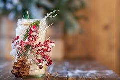 Ο λευκός κάτοχος κεριών διακόσμησε με τον κώνο πεύκων και κόκκινο ashberry στον ξύλινο πίνακα Στοκ Φωτογραφία