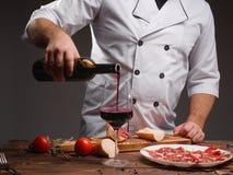 Ο λευκός μάγειρας χύνει το κρασί σε ένα ποτήρι Ένα μπουκάλι του κρασιού, καρυκεύματα, τεμάχισε jamon, ντομάτες, ένας ξύλινος πίνα Στοκ εικόνες με δικαίωμα ελεύθερης χρήσης