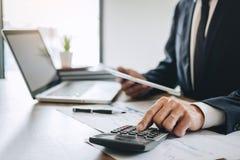 Ο λογιστής επιχειρηματιών που απασχολείται στο νέο πρόγραμμα για το φορητό προσωπικό υπολογιστή με το έγγραφο εκθέσεων και αναλύε στοκ φωτογραφίες