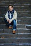 Ο λυπημένος έφηβος κάθεται στα σκαλοπάτια πετρών υπαίθρια στοκ εικόνα