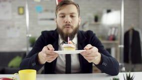 Ο λυπημένος γενειοφόρος επιχειρηματίας, εργαζόμενος γραφείων γιορτάζει μόνα γενέθλια στο γραφείο, φυσά ένα κερί σε έναν μικρό απόθεμα βίντεο