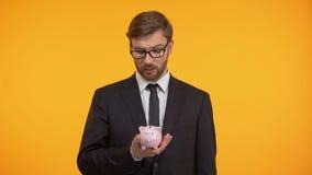 Ο λυπημένος επιχειρηματίας που τινάζει την κενές piggy-τράπεζα, τις υψηλές φορολογίες και την ανεργία, οδηγεί σε πτώχευση απόθεμα βίντεο