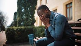 Ο λυπημένος και καταθλιπτικός νέος επιχειρηματίας μαύρων Αφρικανών κάθεται κουρασμένος μετά από την κλήση στην οδό Έννοια των κακ φιλμ μικρού μήκους