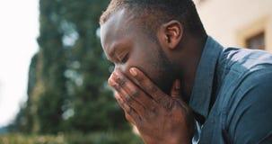 Ο λυπημένος και καταθλιπτικός νέος επιχειρηματίας μαύρων Αφρικανών κάθεται κουρασμένος μετά από την κλήση στην οδό Έννοια των κακ απόθεμα βίντεο