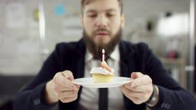 Ο λυπημένος σοβαρός γενειοφόρος επιχειρηματίας, εργαζόμενος γραφείων γιορτάζει μόνα γενέθλια στο γραφείο, φυσά ένα κερί επάνω φιλμ μικρού μήκους