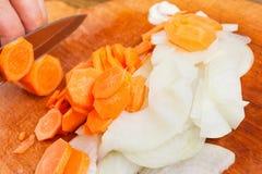Ο μάγειρας έκοψε το κρεμμύδι και το καρότο στον τεμαχίζοντας πίνακα Στοκ Φωτογραφίες