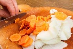 Ο μάγειρας έκοψε το κρεμμύδι και το καρότο στον τεμαχίζοντας πίνακα Στοκ φωτογραφία με δικαίωμα ελεύθερης χρήσης