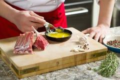 Ο μάγειρας ανακατώνει το κουτάλι με το πετρέλαιο σε ένα τηγανίζοντας τηγάνι Στοκ Εικόνες