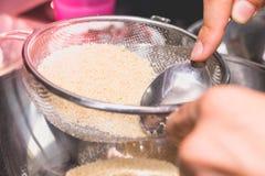 Ο μάγειρας αναμιγνύει και κοσκινίζει τη σκόνη αμυγδάλων στο αλεύρι Στοκ Φωτογραφίες