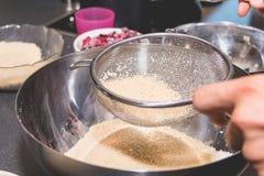 Ο μάγειρας αναμιγνύει και κοσκινίζει τη σκόνη αμυγδάλων στο αλεύρι Στοκ φωτογραφία με δικαίωμα ελεύθερης χρήσης
