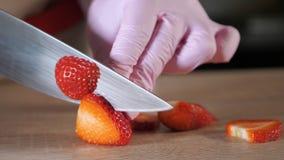 Ο μάγειρας αρχιμαγείρων κόβει τις φράουλες σε έναν τέμνοντα πίνακα απόθεμα βίντεο