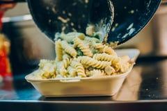 Ο μάγειρας αρχιμαγείρων χύνει τα μακαρόνια στο πλαστικό πακέτο παράδοσης γρήγορου φαγητού στοκ εικόνες