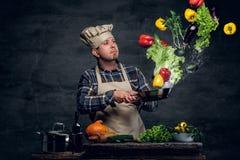 Ο μάγειρας ατόμων κρατά ένα τηγάνι με τα λαχανικά που πετούν στον αέρα Στοκ φωτογραφία με δικαίωμα ελεύθερης χρήσης