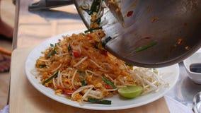 Ο μάγειρας βάζει τα νουντλς με τις γαρίδες στο πιάτο Βαθμιαία μαγειρεύοντας μαξιλάρι Ταϊλανδός Ταϊλανδική κουζίνα closeup 4K απόθεμα βίντεο