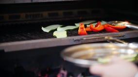Ο μάγειρας βάζει τα τεμαχισμένα πιάτα αγγουριών δίπλα στα κομμάτια του κόκκινου πιπεριού στο φούρνο απόθεμα βίντεο