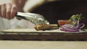 Ο μάγειρας βάζει το πλευρό στο κομμάτι του ψωμιού pita στη στάση απόθεμα βίντεο