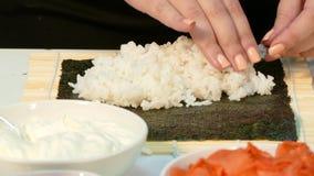 Ο μάγειρας βάζει το ρύζι στο nori φιλμ μικρού μήκους