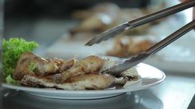 Ο μάγειρας βάζει το τεμαχισμένο τηγανισμένο κοτόπουλο στο πιάτο απόθεμα βίντεο