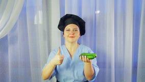 Ο μάγειρας γυναικών στην ποδιά χαμογελά, κρατά τα αγγούρια στο χέρι της και παρουσιάζει την κατηγορία φιλμ μικρού μήκους