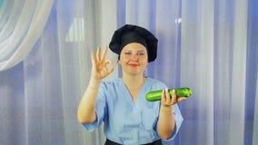 Ο μάγειρας γυναικών στην ποδιά χαμογελά, κρατά τα κολοκύθια κολοκυθιών διαθέσιμα και παρουσιάζει χέρι της ΕΝΤΑΞΕΙ απόθεμα βίντεο