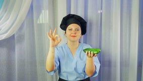 Ο μάγειρας γυναικών στην ποδιά χαμογελά, κρατά τα φρέσκα αγγούρια στο χέρι της και παρουσιάζει χέρι της ΕΝΤΑΞΕΙ φιλμ μικρού μήκους