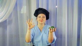 Ο μάγειρας γυναικών στην ποδιά χαμογελά, κρατά το αβοκάντο στο χέρι της και παρουσιάζει ΕΝΤΆΞΕΙ με το χέρι της απόθεμα βίντεο