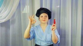 Ο μάγειρας γυναικών στην ποδιά χαμογελά, κρατά το πιπέρι τσίλι στο χέρι της και παρουσιάζει χέρι της ΕΝΤΑΞΕΙ φιλμ μικρού μήκους