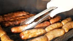Ο μάγειρας γυρίζει τα ψημένα στη σχάρα πλευρά και τα λουκάνικα χοιρινού κρέατος με τις λαβίδες μετάλλων Από κάτω από το πλέγμα πη απόθεμα βίντεο