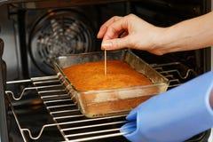 Ο μάγειρας ελέγχει το κέικ ετοιμότητας Στοκ Φωτογραφία