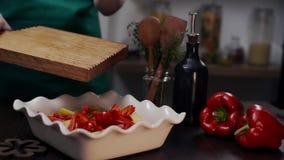Ο μάγειρας κάνει το γεύμα με το κόκκινο πιπέρι κουδουνιών και άλλα λαχανικά, αρχιμάγειρας προσθέτουν το πιπέρι κουδουνιών στο γεύ απόθεμα βίντεο