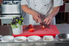 Ο μάγειρας κόβει μια ντομάτα με ένα μαχαίρι στην κουζίνα Στοκ Εικόνες