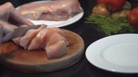 Ο μάγειρας κόβει το στήθος κοτόπουλου στο μισό, ακατέργαστο κοτόπουλο, στήθη κοτόπουλου μαγείρων αρχιμαγείρων, κρέας πουλερικών,  απόθεμα βίντεο