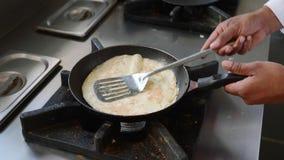 Ο μάγειρας προετοιμάζει μια ομελέτα στο τηγάνισμα του τηγανιού, κινημ απόθεμα βίντεο