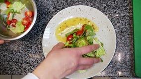 Ο μάγειρας προετοιμάζει μια σαλάτα σε ένα εστιατόριο, σχεδιάζει σε ένα πιάτο με το χέρι του φιλμ μικρού μήκους