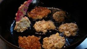 Ο μάγειρας προετοιμάζει cutlets σε ένα τηγανίζοντας τηγάνι Οι μικρές τηγανίτες είναι τηγανισμένες στο πετρέλαιο απόθεμα βίντεο