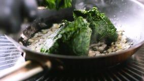 Ο μάγειρας προσθέτει το σπανάκι στο τηγανισμένο κρεμμύδι στο τηγάνι απόθεμα βίντεο