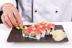 Ο μάγειρας προσθέτει το wasabi και την πιπερόριζα στους ρόλους σουσιών Στοκ Φωτογραφίες