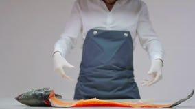 Ο μάγειρας ρίχνει ένα μεγάλο ψάρι με έναν βουρτσισμένο κορμό στον πίνακα απόθεμα βίντεο