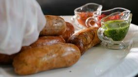 Ο μάγειρας ρυθμίζει προσεκτικά τα έτοιμα λουκάνικα σε ένα πιάτο κοντά στις διάφορες σάλτσες Πιάτα κρέατος της σχάρας φιλμ μικρού μήκους